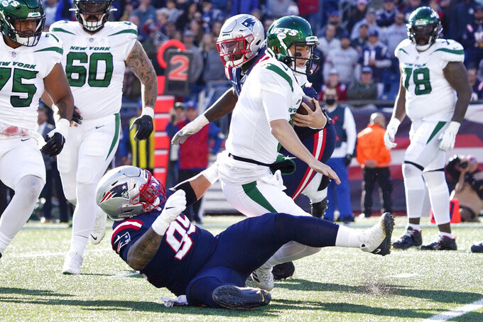 New York Jets quarterback Mike White is taken down by New England Patriots defensive lineman Daniel Ekuale (95) during the first half of an NFL football game, Sunday, Oct. 24, 2021, in Foxborough, Mass. (AP Photo/Mary Schwalm)