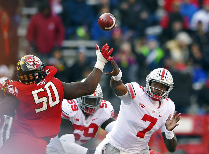 Ohio State quarterback Dwayne Haskins Jr. (7) passes under pressure from Maryland linebacker Mbi Tanyi (50) during the second half of an NCAA football game, Saturday, Nov. 17, 2018, in College Park, Md. Ohio State won 52-51 in overtime. (AP Photo/Nick Wass)