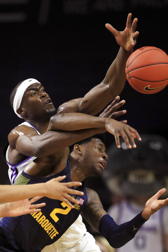 Kansas State forward Makol Mawien, left, tries to rebound over Marquette guard Sacar Anim (2) during the first half of an NCAA college basketball game in Manhattan, Kan., Saturday, Dec. 7, 2019. (AP Photo/Orlin Wagner)
