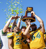 North Dakota State's Jaylaan Wimbush (23), Colin Conner (64), and Tanner Volson (74) hoist the trophy after beating Eastern Washington 38-24 in the FCS championship NCAA college football game, Saturday, Jan. 5, 2019, in Frisco, Texas. North Dakota State won 38-24. (AP Photo/Jeffrey McWhorter)