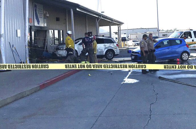 Deputies and firefighters stand outside the Red Bluff Walmart distribution center after a man reportedly opened fire there and rammed his vehicle into the building, Saturday, June 27, 2020, in Red Bluff, Calif. (Damon Arthur/The Record Searchlight via AP)