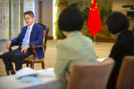 Staff members watch as Chinese Vice Minister of Foreign Affairs Le Yucheng speaks during an interview with the Associated Press at the Ministry of Foreign Affairs in Beijing, Friday, April 16, 2021. Le spoke to AP on a wide range of issues during an interview on Friday including climate change and US-China relations. (AP Photo/Mark Schiefelbein)