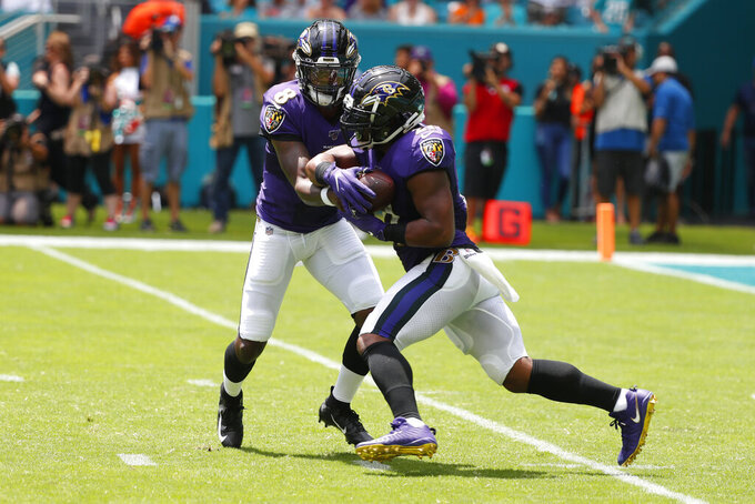 Baltimore Ravens quarterback Lamar Jackson (8) hands the ball to running back Mark Ingram (21), during the first half at an NFL football game against the Miami Dolphins, Sunday, Sept. 8, 2019, in Miami Gardens, Fla. (AP Photo/Wilfredo Lee)