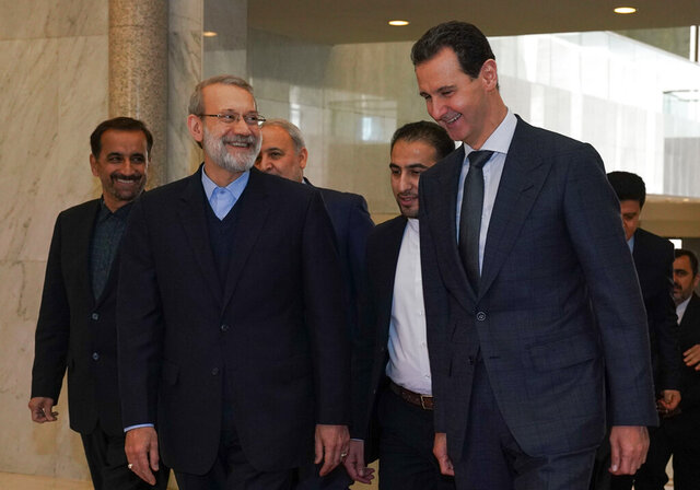 In this photo released by the Syrian official news agency SANA, Syrian President Bashar Assad, right, speaks to Iran's Parliament Speaker Ali Larijani, in Damascus, Syria, Sunday, Feb. 16, 2020. (SANA via AP)