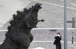 A woman adjusts her face mask as she walks by a statue of Godzilla in Tokyo Friday, Oct. 16, 2020. The Japanese capital confirmed more than 180 new coronavirus cases on Friday. (AP Photo/Hiro Komae)