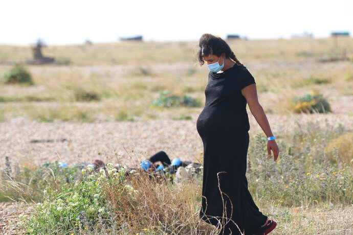 A pregnant woman among a group of migrants as they rest on the beach waiting for Uk Border Force officials at Dungeness, southern England, Thursday Aug. 6 2020.  The British government says it will strengthen border measures as calm summer weather has prompted a record number of people to attempt the risky sea crossing in small vessels, from northern France to England. (AP Photo / Susan Pilcher)