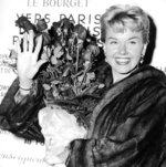 FILE - In this April 15, 1955 file photo, American actress and singer Doris Day holds a bouquet of roses at Le Bourget Airport in Paris, France after flying in from London. Day, whose wholesome screen presence stood for a time of innocence in '60s films, has died, her foundation says. She was 97. The Doris Day Animal Foundation confirmed Day died early Monday, May 13, 2019, at her Carmel Valley, California, home. (AP Photo, File)