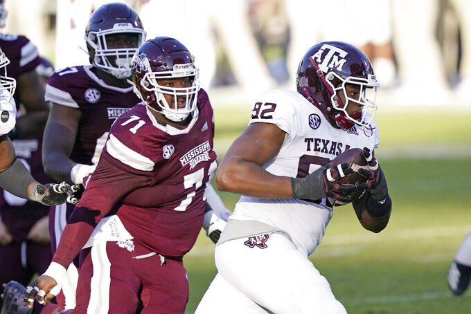 Texas A&M defensive lineman Jayden Peevy (92) recovers a fumble and is pursued by Mississippi State offensive lineman James Jackson (71) during the second half of an NCAA college football game in Starkville, Miss., Saturday, Oct. 17, 2020. Peevy did not score.  (AP Photo/Rogelio V. Solis)