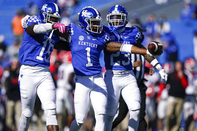 Kentucky defensive back Kelvin Joseph (1) celebrates with linebacker Jordan Wright (15) and defensive back Tyrell Ajian (23) after his interception during the second half of an NCAA college football game against Georgia, Oct. 31, 2020, in Lexington, Ky. (AP Photo/Bryan Woolston)