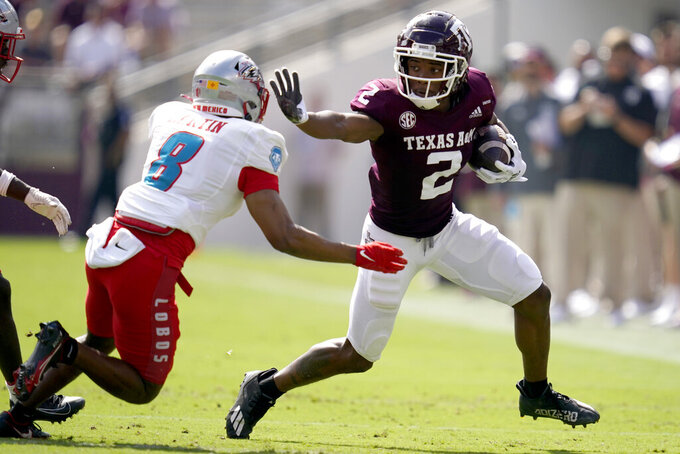 Texas A&M wide receiver Chase Lane (2) stiff arms New Mexico cornerback Donte Martin (8) during a first down run during the first quarter of an NCAA college football game on Saturday, Sept. 18, 2021, in College Station, Texas. (AP Photo/Sam Craft)