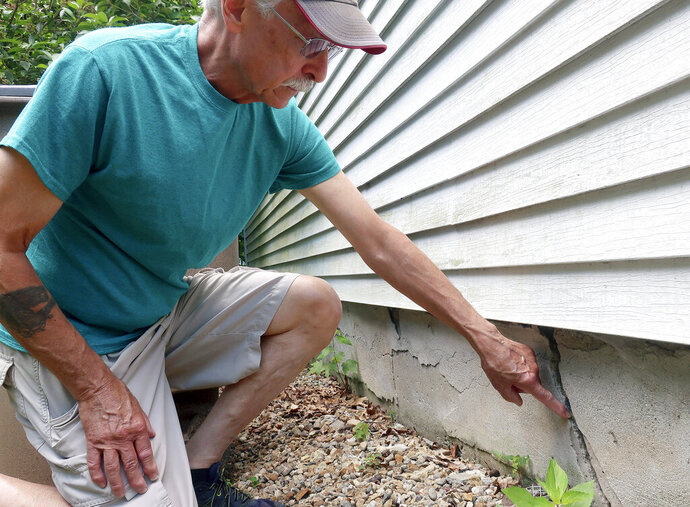 In this July 1, 2019 photo, Ken Fisher points to one of the cracks in the foundation of his home in Vernon, Conn. The foundation of his home is deteriorating due to the presence of an iron sulfide called pyrrhotite in what has been called a slow-moving disaster, the first of its kind in the United States. Hundreds of suburban homeowners in a large swath of central Connecticut are getting help through a new state assistance program to salvage property that had been doomed by a bad batch of concrete. (AP Photo/Ted Shaffrey)