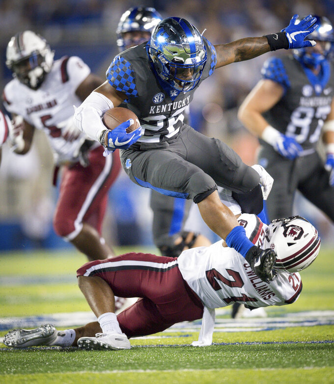 FILE - In this Sept. 29, 2018, file photo, Kentucky running back Benny Snell Jr. (26) leaps over South Carolina defensive back Jamyest Williams (21) during the first half of an NCAA college football game in Lexington, Ky. The Georgia Bulldogs must run a gauntlet of four straight games against Southeastern Conference opponents currently ranked in the Top 25. LSU, Florida, Kentucky and Auburn. (AP Photo/Bryan Woolston, File)