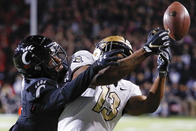 Cincinnati cornerback Coby Bryant, left, breaks up a pass to UCF wide receiver Gabriel Davis (13) during the second half of an NCAA college football game Friday, Oct. 4, 2019, in Cincinnati. (AP Photo/John Minchillo)