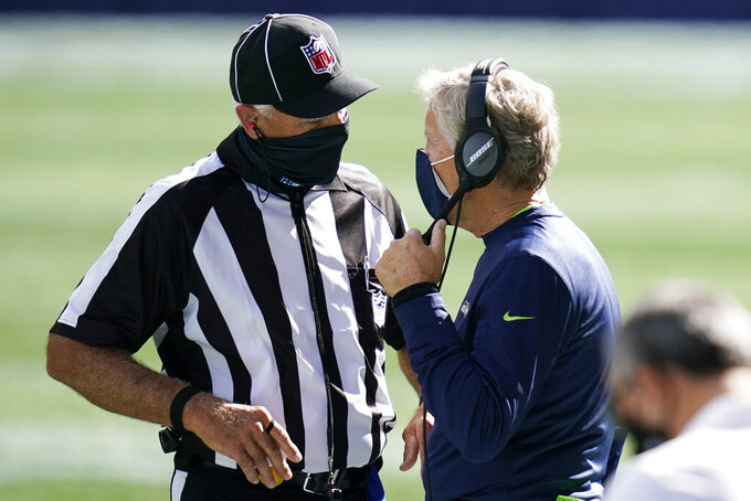 Seattle Seahawks head coach Pete Carroll wears a mask as he talks to an official during the first half of an NFL football game against the Dallas Cowboys, Sunday, Sept. 27, 2020, in Seattle. (AP Photo/Elaine Thompson)