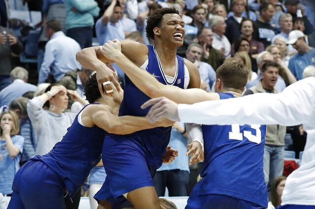 Duke forward Wendell Moore Jr., center, celebrates with guard Jordan Goldwire and forward Joey Baker (13) following Moore's game-winning shot in overtime of an NCAA college basketball game against North Carolina in Chapel Hill, N.C., Saturday, Feb. 8, 2020. (AP Photo/Gerry Broome)