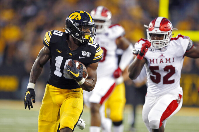 Iowa running back Mekhi Sargent runs from Miami of Ohio defensive lineman Cam Turner (52) during the first half of an NCAA college football game, Saturday, Aug. 31, 2019, in Iowa City, Iowa. (AP Photo/Charlie Neibergall)