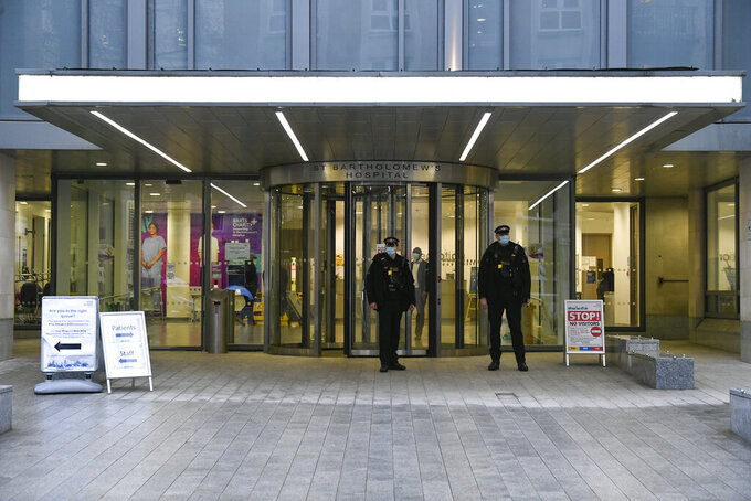 Police officers stand outside the main entrance of the St Bartholomew's Hospital where Britain's Prince Philip is being treated, in London, Thursday, March 4, 2021. Buckingham Palace said Philip, the 99-year-old husband of Queen Elizabeth II, was transferred from King Edward VII's Hospital to St Bartholomew's Hospital on Monday to undergo testing and observation for a pre-existing heart condition as he continues treatment for an unspecified infection.(AP Photo/Alberto Pezzali)