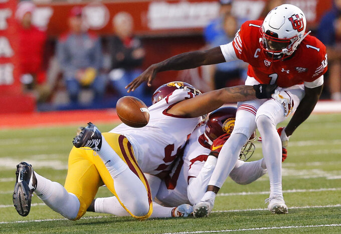 Utah quarterback Tyler Huntley (1) fumbles the ball after being tackled by Southern California linebacker Hunter Echols, left, and John Houston Jr., center, in the first half of an NCAA college football game Saturday, Oct. 20, 2018, in Salt Lake City. (AP Photo/Rick Bowmer)