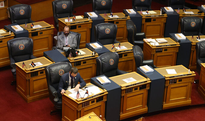 FILE - In this May 26, 2020, file photo, state Sen. Steve Fenberg, D-Boulder, front, and Sen. Robert Rodriguez, D-Denver, sit amid the empty desks before the chamber reopens in downtown Denver. Colorado's Democrat-led Legislature is plowing ahead on special session legislation to provide limited state relief to businesses, students, and others affected by the coronavirus pandemic. The Senate on Tuesday, Dec. 1, 2020, unanimously passed bills to direct $5 million to help residents to pay utility bills; $50 million to assist landlords and tenants; and $100 million to the governor's office for use in the public health emergency. (AP Photo/David Zalubowski, File)