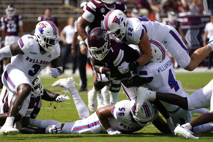 Mississippi State running back Jo'quavious Marks (7) is gang tackled by Louisiana Tech defenders, including linebacker Tyler Grubbs (52) and defensive back BeeJay Williamson (4) during the first half of an NCAA college football game in Starkville, Miss., Saturday, Sept. 4, 2021. (AP Photo/Rogelio V. Solis)
