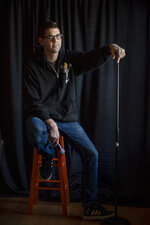 Comedian Brad Pierce poses for a photo at a friend's house in front of a portable backdrop he uses for gigs in Warwick, R.I., Friday, Jan. 8, 2021. Pierce was finally doing well with his comedy when the pandemic hit. Now he wonders if he can possibly build up his career again. He has a friend who drives for Amazon and fears having to get a job like that while talking about the good old days when he was an entertainer. (AP Photo/David Goldman)