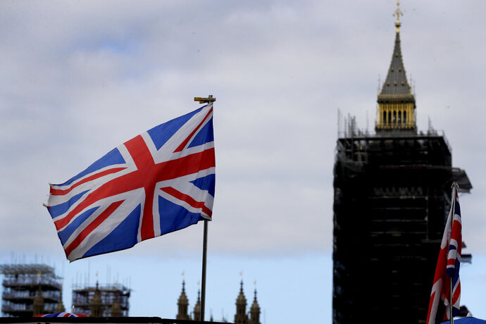 """The Union flag flies above a souvenir stand in front of Big Ben in London, Friday, Oct. 16, 2020. Britain's foreign minister says there are only narrow differences remaining in trade talks between the U.K. and the European Union. But Dominic Raab insists the bloc must show more """"flexibility"""" if it wants to make a deal. (AP Photo/Kirsty Wigglesworth)"""