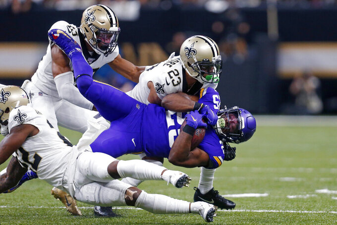 Minnesota Vikings running back Alexander Mattison (25) is tackled by New Orleans Saints cornerback Marshon Lattimore (23) in the first half of an NFL wild-card playoff football game, Sunday, Jan. 5, 2020, in New Orleans. (AP Photo/Butch Dill)