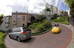 Cars make their way down Lombard Street in San Francisco, Monday, April 15, 2019. Thousands of tourists may soon have to pay as much as $10 to drive down the world-famous crooked street if a proposal announced Monday becomes law. In the summer months, an estimated 6,000 people a day visit the 600-foot-long street, creating lines of cars that stretch for blocks. (AP Photo/Eric Risberg)