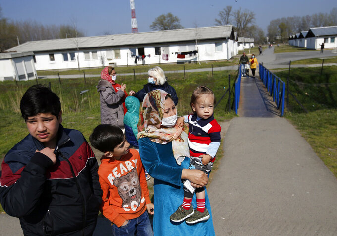 """Migrants wait in garden during the vaccination in the """"Krnjaca"""" refugee centre near Belgrade, Serbia, Friday, March 26, 2021. Serbia has started vaccinating migrants as the Balkan country struggles with a new coronavirus outbreak despite a widespread inoculation campaign. (AP Photo/Darko Vojinovic)"""