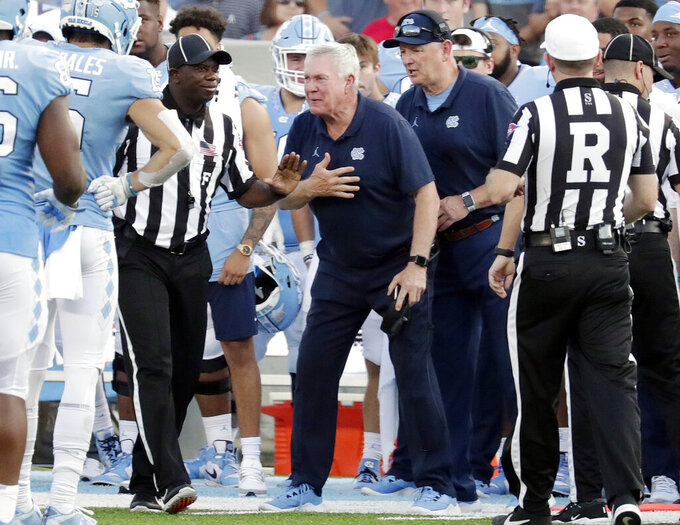 North Carolina head coach Mack Brown, center, argues a call with the officials during the third quarter of an NCAA college football game against Appalachian State in Chapel Hill, N.C., Saturday, Sept. 21, 2019. (AP Photo/Chris Seward)