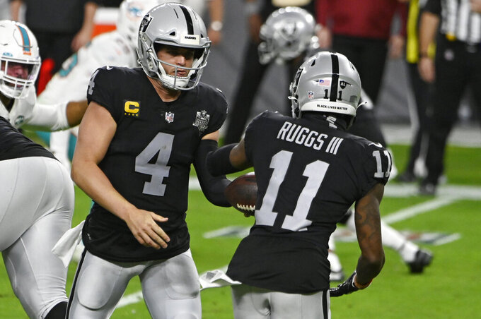 Las Vegas Raiders quarterback Derek Carr (4) hands the ball off to wide receiver Henry Ruggs III (11) during the first half of an NFL football game against the Miami Dolphins, Saturday, Dec. 26, 2020, in Las Vegas. (AP Photo/David Becker)