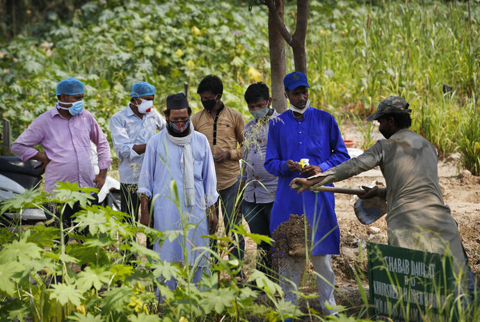 Relatives and health workers pay their respects as the body of a three-month-old COVID-19 victim is buried in New Delhi, India, Wednesday, Sept. 16, 2020. India's total of coronavirus infections passed 5 million Wednesday, still soaring and testing the feeble health care system in tens of thousands of impoverished towns and villages. (AP Photo/Manish Swarup)