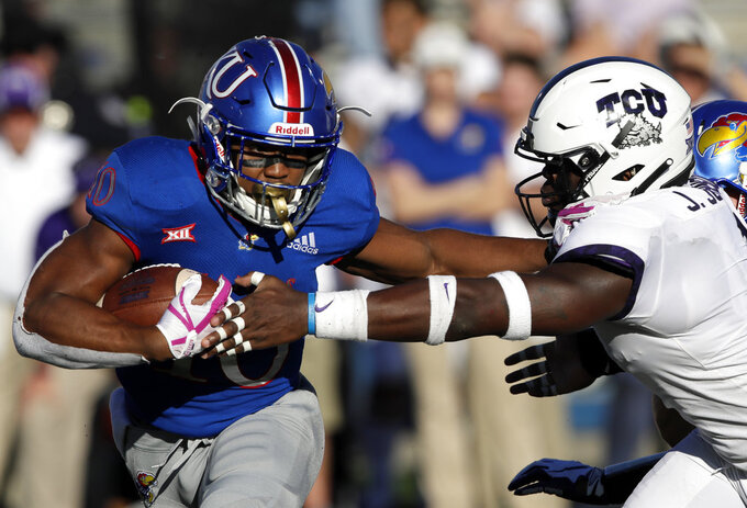 Kansas running back Khalil Herbert (10) stiff arms TCU linebacker Jawuan Johnson, right, during the second half of an NCAA college football game in Lawrence, Kan., Saturday, Oct. 27, 2018. (AP Photo/Orlin Wagner)