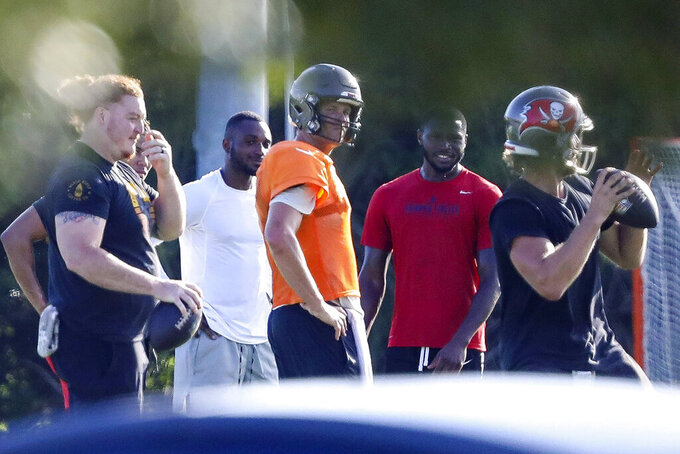 Tampa Bay Buccaneers center Ryan Jensen, far left, along with safety Mike Edwards, second from left, quarterback Tom Brady, center in orange, cornerback Jamel Dean, second from right, and quarterback Blaine Gabbert are seen during a private workout Tuesday, June 23, 2020, at Berkeley Preparatory School in Tampa, Fla. (Chris Urso/Tampa Bay Times via AP)