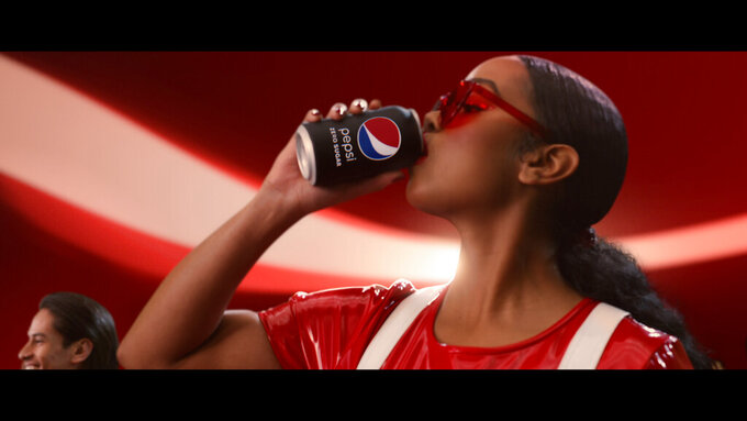"""This undated image provided by PepsiCo shows H.E.R. in a scene from the company's 2020 Super Bowl NFL football spot. Pepsi tries to reignite the Cola Wars with Missy Elliott and H.E.R. performing an updated version of """"Paint it Black"""" that starts with a red cola can that looks like a Coke changing into a black can of Pepsi Zero Sugar to the lyrics of """"I see a red door and I want it painted black.""""(PepsiCo via AP)"""