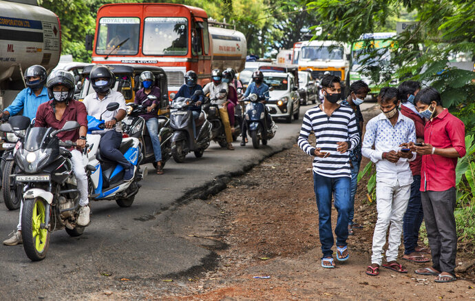 Commuters wearing masks wait at a traffic intersection in Kochi, Kerala state, India, Monday, Sept.28, 2020. India's confirmed coronavirus tally has crossed 6 million cases, only second behind the United States, as the south Asian country continues to battle the worst COVID-19 outbreak in the world. (AP Photo/R S Iyer)