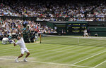 Switzerland's Roger Federer, left, serves to Serbia's Novak Djokovic, right, during the men's singles final match of the Wimbledon Tennis Championships in London, Sunday, July 14, 2019. (AP Photo/Ben Curtis)