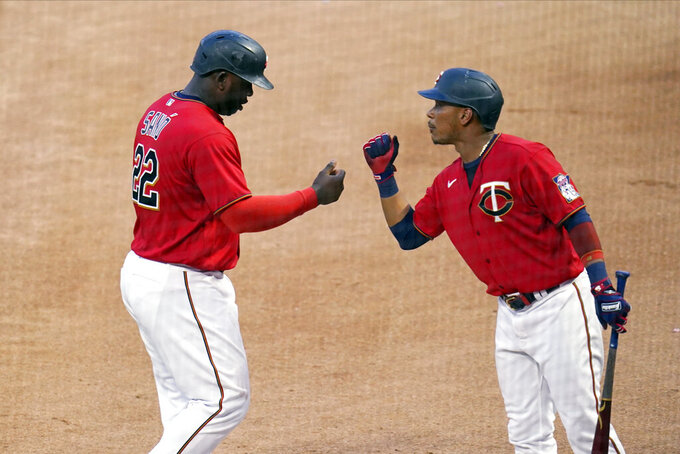 Minnesota Twins' Miguel Sano (22) and Jorge Polanco bump fists after Sano scored on an Andrelton Simmons double off New York Yankees pitcher Michael King during the fourth inning of a baseball game Thursday, June 10, 2021, in Minneapolis. (AP Photo/Jim Mone)