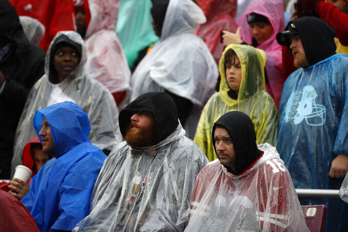 Spectators watch the first half of an NFL football game between the San Francisco 49ers and the Washington Redskins as rain falls, Sunday, Oct. 20, 2019, in Landover, Md. (AP Photo/Alex Brandon)