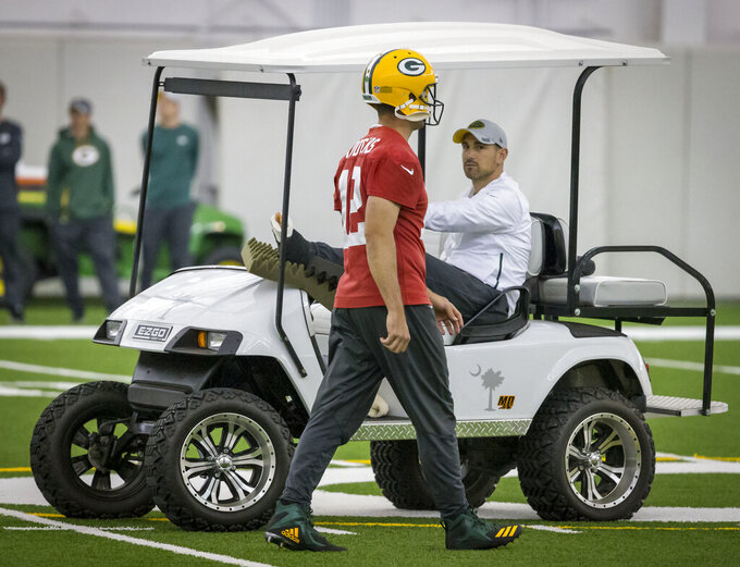 FILE - In this June 12, 2019, file photo, quarterback Aaron Rodgers, left, walks past head coach Matt LaFleur during an NFL football practice in Green Bay, Wisc. LeFleur is recovering from a torn Achilles. LaFleur opens his first training camp as Packers head coach with his biggest issue being the nagging Achilles injury. LaFleur said Wednesday, July 24, 2019, that he hopes to be out of his walking boot in the next couple weeks as he continues to recover from a ruptured Achilles tendon he suffered in May. As for his on-field concerns and relationship with quarterback Aaron Rodgers, Lafleur says he enjoys the challenge of coaching Rodgers and called the two-time NFL MVP one of the most competitive players he's ever been around. (AP Photo/Mike Roemer, File)