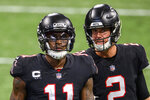 FILE - Atlanta Falcons quarterback Matt Ryan (2) speaks with wide receiver Julio Jones (11) during the second half of an NFL football game against the New Orleans Saints, in Atlanta, in this Sunday, Dec. 6, 2020, file photo. The Atlanta Falcons began their offseason training program Tuesday, May 25, 20921, without longtime star receiver Julio Jones, who apparently has no intention of returning to a rebuilding team that is still struggling to get under the salary cap. (AP Photo/Danny Karnik, FIle)