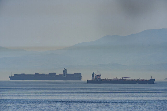 A view of the vessel the Clavel, right, sailing on international waters crossing the Gibraltar stretch on Wednesday, May 20, 2020. Five Iranian tankers likely carrying at least $45.5 million worth of gasoline and similar products are now sailing to Venezuela, part of a wider deal between the two U.S.-sanctioned nations amid heightened tensions between Tehran and Washington. (AP Photo/Marcos Moreno)