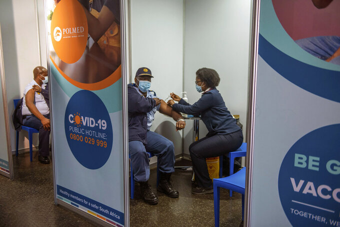 FILE - In this July 5 2021, file photo a policeman receives his Johnson & Johnson COVID-19 vaccine in Soweto, South Africa. South Africa's COVID-19 vaccination campaign is regaining momentum after being disrupted earlier this month by a week of riots following the imprisonment of former President Jacob Zuma. (AP Photo/Alet Pretorius, File)