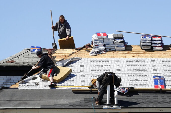 Roofers work on removing and placing new shingles in Warren, Mich., Thursday, April 2, 2020. The coronavirus COVID-19 outbreak has triggered a stunning collapse in the U.S. workforce with 10 million people losing their jobs in the past two weeks and economists warn unemployment could reach levels not seen since the Depression, as the economic damage from the crisis piles up around the world. (AP Photo/Paul Sancya)