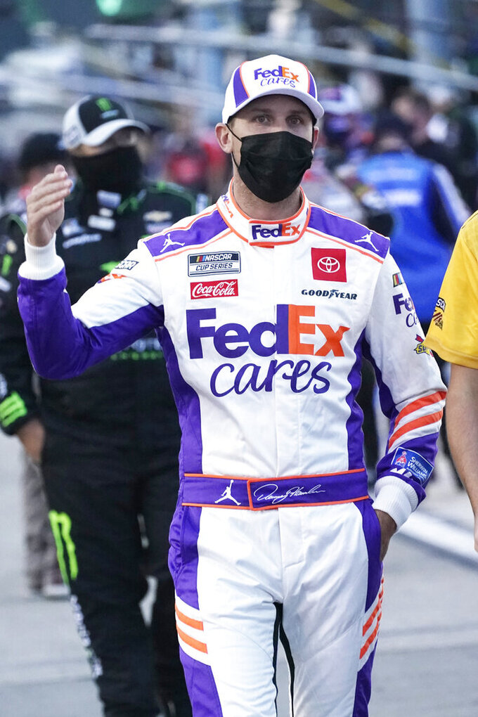 Denny Hamlin walks to his car prior to the start of a NASCAR Cup Series auto race Saturday, Sept. 12, 2020, in Richmond, Va. (AP Photo/Steve Helber)