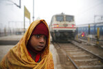 A boy looks down the tracks as he waits at the Lucknow, India train station during a cold and foggy morning, on Thursday, Jan. 11, 2018. (AP Photo/Rajesh Kumar Singh)