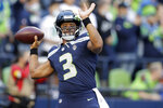Seattle Seahawks quarterback Russell Wilson warms up for the team's NFL football preseason game against the Los Angeles Chargers, Saturday, Aug. 28, 2021, in Seattle. (AP Photo/John Froschauer)