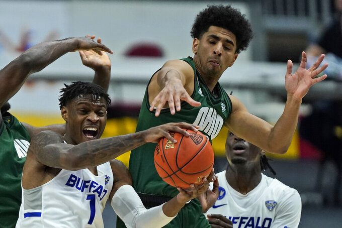 Buffalo's LaQuill Hardnett, left, grabs a rebound ahead of Ohio's Ben Roderick during the second half of an NCAA college basketball game in the championship of the Mid-American Conference tournament, Saturday, March 13, 2021, in Cleveland. (AP Photo/Tony Dejak)