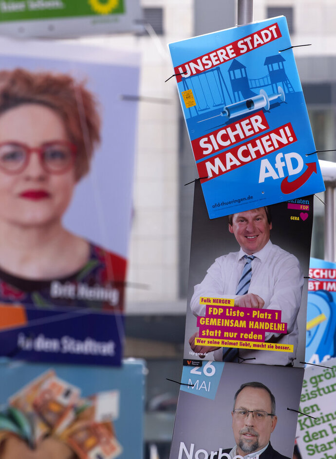 In this Friday, May 17, 2019 photo an AfD poster (top right) hangs on a street light during the street Europe and communal election campaigning of the far-right Alternative for Germany AfD in Gera, Germany. In Germany, the far-right AfD party is dominating the social media campaigns ahead of the European elections with attacks on the political establishment and fearmongering of migrants and Islam. The question is if their skilled digital campaigns will translate into a political success when Germany's voters cast their ballot on May 26. (AP Photo/Jens Meyer)