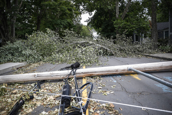 FILE- In this Aug. 7, 2020 file photo, power lines and poles lie in a roadway beside a fallen tree in Westport, Conn., brought down by Tropical Storm Isaias. On Wednesday, Oct. 21, 2020, Connecticut Attorney General William Tong asked regulators to order reimbursements for utility customers who lost food and medicine during August's days-long power outage in the wake of Tropical Storm Isaias. (AP Photo/John Minchillo, File)